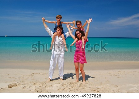 Happy family with two children on beautiful tropical beach. Family vacation - stock photo