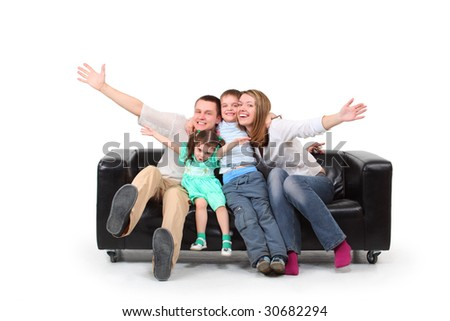 Happy family with two children on black leather sofa - stock photo