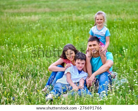 Happy family  with two children on green grass. Outdoor. - stock photo