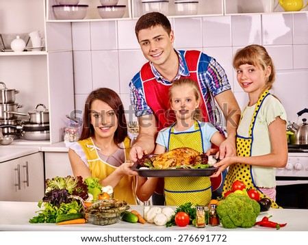 Happy family with two daughter at kitchen. Cooking chicken. - stock photo