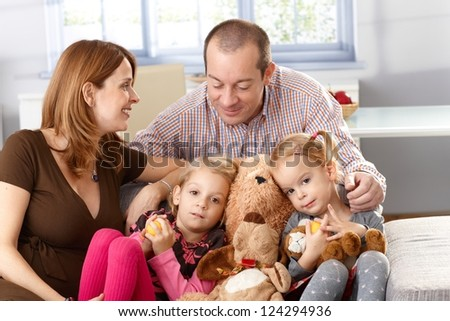 Happy family with two daughters and pregnant mother sitting on sofa. - stock photo