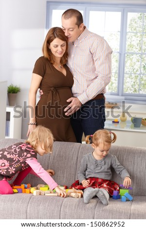 Happy family with two daughters expecting baby, mother and father hugging each other. - stock photo