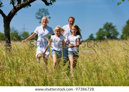 Happy Family with two girls running in a meadow in summer - stock photo