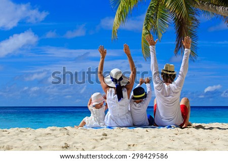 happy family with two kids hands up on the beach - stock photo