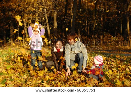 Happy family with two kids having fun in autumn park - stock photo