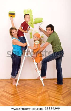 Happy family with two kids holding brushes and painting rolls redecorating their home together - stock photo