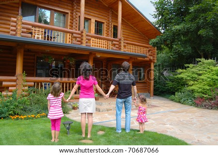 Happy family with two kids looking at the wooden house - stock photo