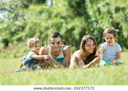 Happy family with two kids lying on grass in sunny summer park. Focus on man