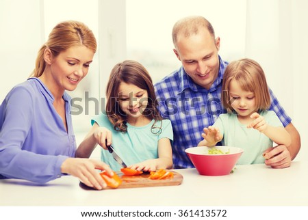 happy family with two kids making dinner at home - stock photo