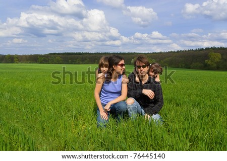 Happy family with two kids on green field - stock photo