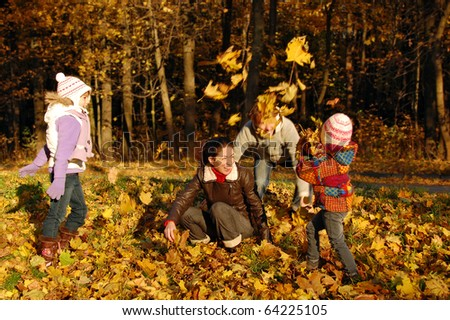 Happy family with two kids throwing leaves in autumn park - stock photo