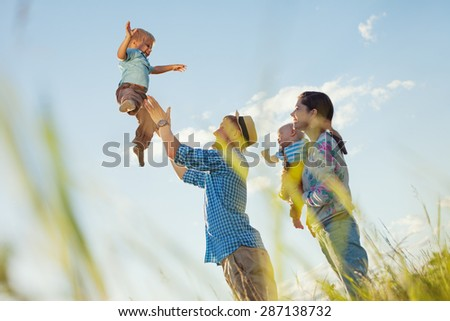 happy family with two sons spending time in the park (lens focus on father and son) - stock photo