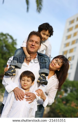 Happy family with two sons together outdoors. Shallow DOF. - stock photo