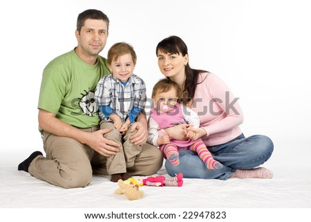 Happy family with two young children sat on floor, white studio background. - stock photo