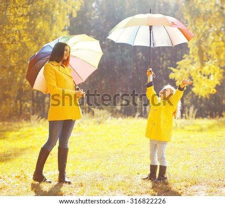 Happy family with umbrellas in sunny autumn rainy day, mother and child enjoying rain - stock photo