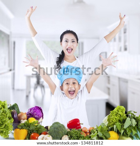 Happy family with vegetable at home - stock photo