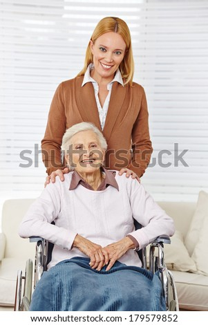 Happy family with woman and senior citizen in a wheelchair - stock photo