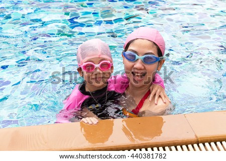 Happy family, young active mother and adorable little daughter having fun in a swimming pool enjoying summer vacation - stock photo