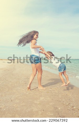 Happy family. Young beautiful  mother and her daughter having fun on the beach. Positive human emotions, feelings, joy. - stock photo