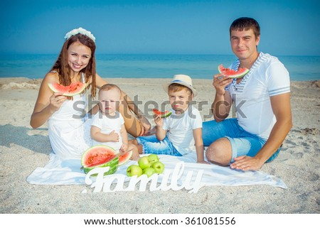 Happy family. Young beautiful  parents and their children having fun on the beach. Positive human emotions, feelings. Eats watermelon
