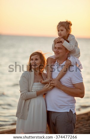 Happy family: young beautiful pregnant woman, a young man and their cute little daughter walking along the sea on a Sunny summer day. Nature in the country.