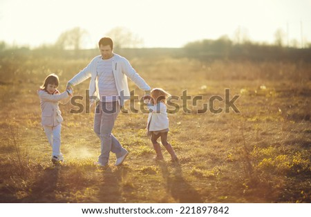 Happy family: young father with his little children walking in the field in summer morning. Strong healthy daddy spinning with his daughter and his son.
