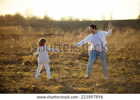 Happy family: young father with his little son walking in the field in summer morning.  - stock photo