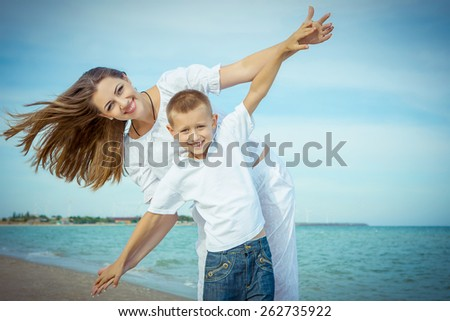 Happy family. Young happy beautiful  mother and her son having fun on the beach. Positive human emotions, feelings, emotions - stock photo