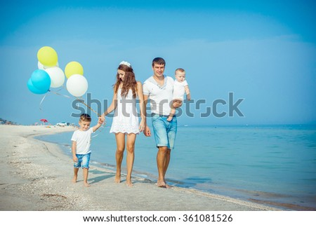 Happy family. Young happy beautiful  parents and their children having fun on the beach. Positive human emotions, feelings. - stock photo