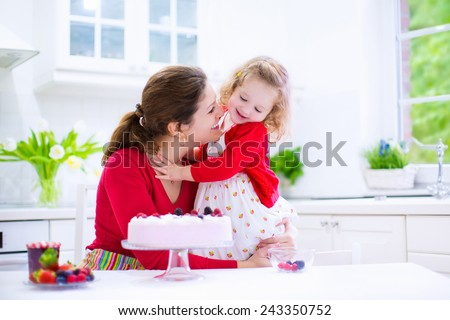 Happy family, young mother and her adorable little daughter, cute curly toddler girl in a red dress, baking fresh strawberry cream cake with fruit and berry in a white kitchen on a sunny summer day - stock photo