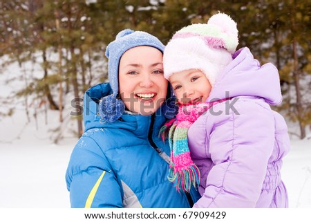 happy family; young mother and her daughter having fun in the winter park (focus on the child)