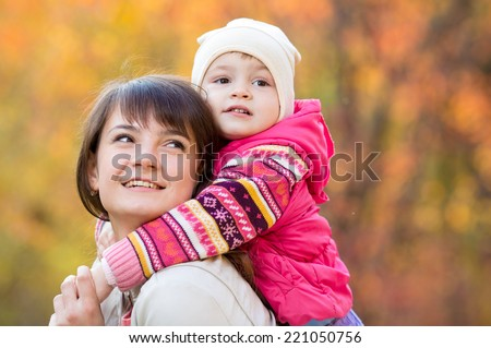 happy family - young mother and kid girl together outdoors in fall - stock photo