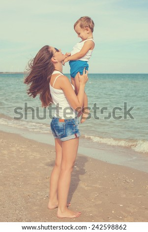Happy family. Young mother throws up baby in the sky, on sunny day. Portrait mother and little son on the beach. Positive human emotions, feelings, emotions. - stock photo