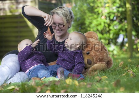 happy family. young mother with her identical twin daughters having fun at the garden - stock photo
