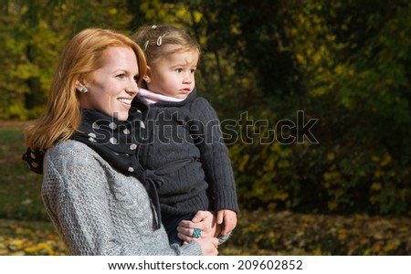 Happy family: young mother with her little girl making a walk in autumn.