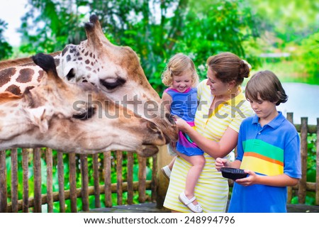 Happy family, young mother with two children, cute laughing toddler girl and a teen age boy feeding giraffe during a trip to a city zoo on a hot summer day - stock photo