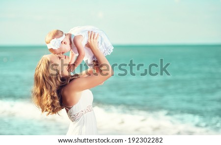 happy familyin white dress. Mother throws up  baby in the sky in beach - stock photo