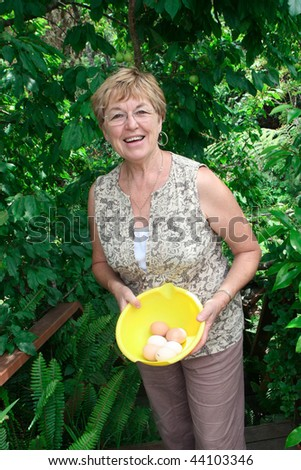 Happy farmer collecting eggs on the farm. - stock photo