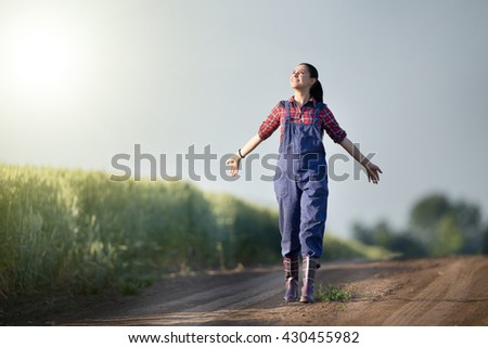 Happy farmer girl walking beside green wheat field with stretched arms and enjoying the sun