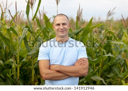 Happy  farmer in field of corn - stock photo