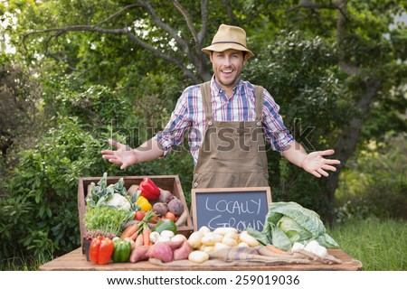 Happy farmer showing his produce on a sunny day - stock photo