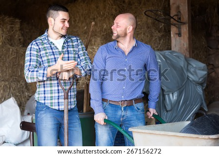 Happy farmers working in a barn. One man is leaning on a pitchfork and another is pushing a wheelbarrow - stock photo