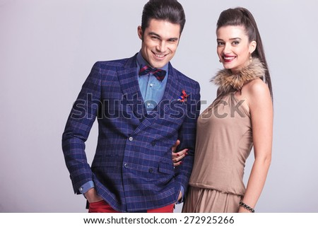Happy fashion couple posing together while smiling to the camera. - stock photo