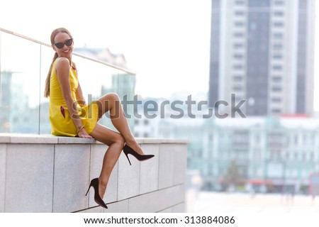Happy fashion girl posing for photographer in the city. Lady with red lips sitting on brick wall and looking at the camera. - stock photo