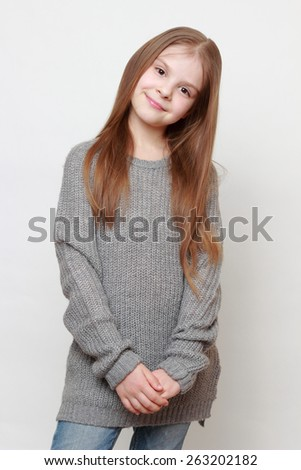 Happy fashion little girl wearing jeans and sweater - stock photo