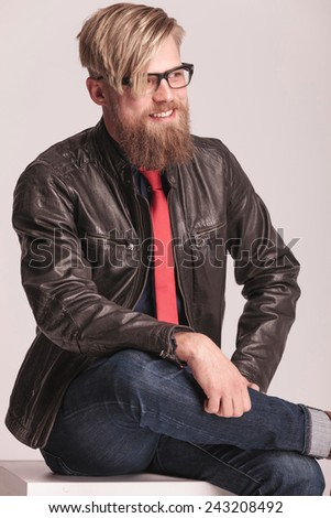 Happy fashion man sitting and smiling while looking away from the camera. He is holding his legs crossed. - stock photo
