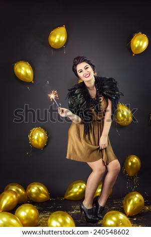 Happy fashion woman dancing, holding fireworks dressed in a gold dress and feathers collar, surrounded with yellow balloons. New Year's Eve Party - stock photo