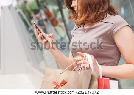 Happy fashion woman with a bag using mobile phone at shopping center. At the background showcase for copy space text - stock photo