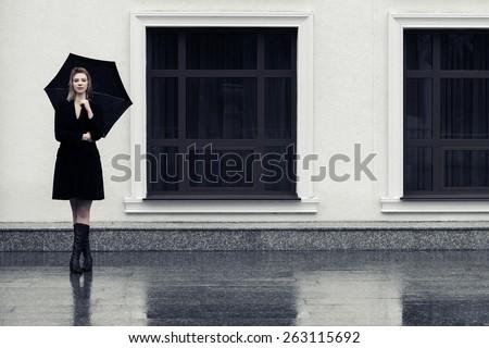 Happy fashion woman with umbrella in the rain - stock photo