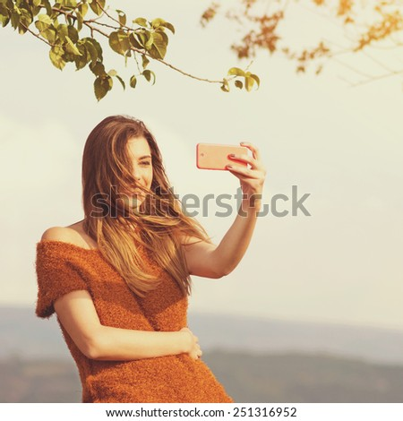 Happy fashionable young Caucasian brunette woman taking a selfie with smartphone in park on windy summer day. Square format, instagram look filter, retouched, warm tones. - stock photo